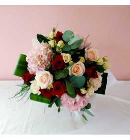 Blush roses with greenery in a cube